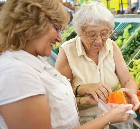 Home Helper Caregiver and elderly bagging vegetables