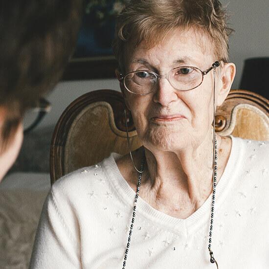 senior and caretaker sitting and talking together