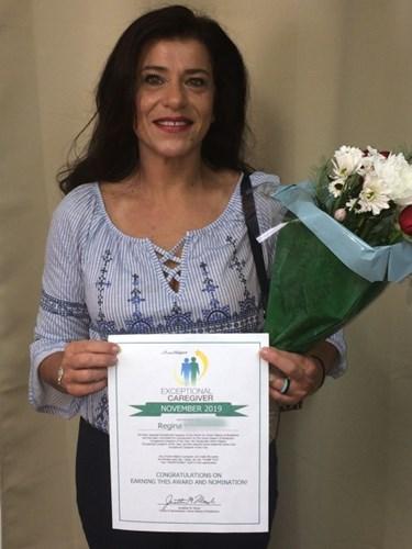 Regina Holding an Exceptional Caregiver Certificate