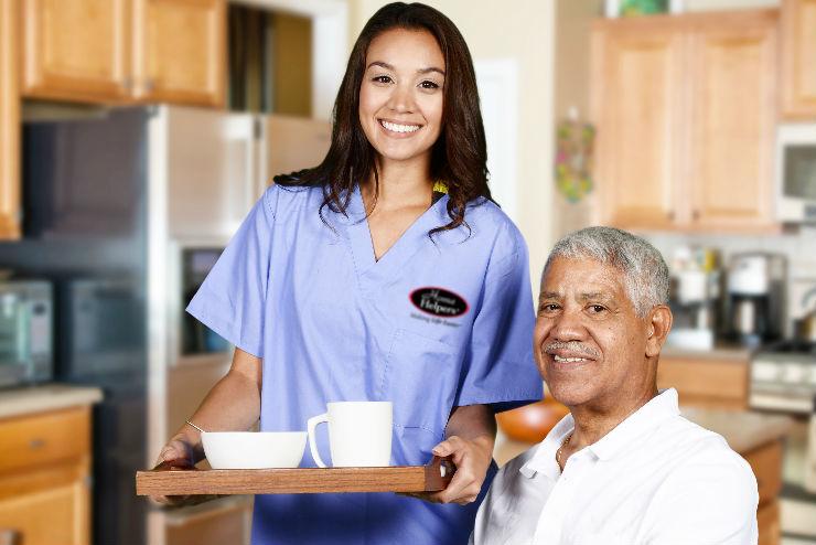caregiver serving elderly man breakfast
