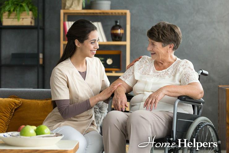 caretaker assisting elderly woman on wheel cahir