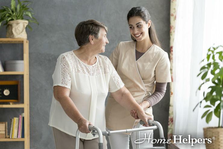 Caregiver assisting elderly woman using a walker